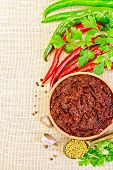 image of fenugreek  - Tabasco adjika in a clay cup hot pepper garlic parsley fenugreek on the background of sack cloth - JPG