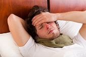 image of laying-in-bed  - Young man having a flu lying in bed - JPG