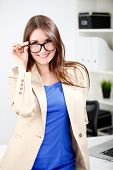 woman wearing glasses posing in office dress