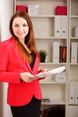 young woman holding sheaf of paperwork standing in office