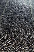 Rolling stones pavement soil texture in Altea Alicante mediterranean village of Spain