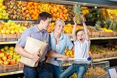 Family against shelves of fruits goes shopping. Father keeps a packet with fruits and vegetables, so