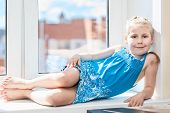 Joyful Young Child Laying On Window Sill In Sun Light