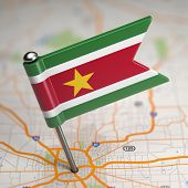 Suriname Small Flag on a Map Background.