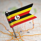 Uganda Small Flag on a Map Background.