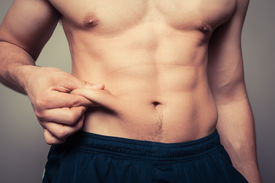 stock photo of skinny fat  - Fit young man pinching the fat on his stomach - JPG