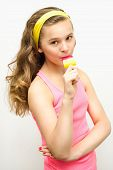 beautiful young girl eating popsicles on a light background