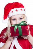 stock photo of fancy-dress  - Pretty blonde female Santa Clause holding wrapped Christmas gift with green ribbon wearing fancy dress costume - JPG