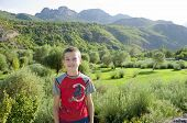 KELMEND, ALBANIA - AUGUST, 10 2013: a smiling child is posing on the blurred background of an idyllic landscape in the Kelmend District of the north Albania.