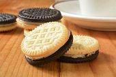 picture of duplex  - Closeup of duplex cream filled sandiwch cookies with a cup of coffee - JPG
