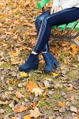 beautiful legs girl in black pants and boots sitting on the bench in autumn Park