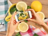 Woman taking photo of tea with lemon with smartphone