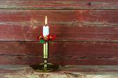 A White Candle In A Candlestick Of Bronze