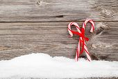 Colorful Striped Red And White Xmas Candy Canes With Winter Snow On Wooden Boards