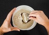 Person Using A Measurement Tool In A Bowl Of Wheat Flour