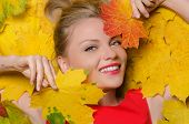 Young Woman In Yellow Autumn Maple Leaves