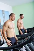 Two Handsome Men In Gym Running On The Ergometer