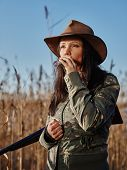 picture of shotgun  - Waterfowl hunting the female hunter carry a shotgun and she use a duck call blue sky and reeds on background - JPG