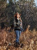 image of shotgun  - Waterfowl hunting the female hunter carry a shotgun autumnal bushes on background - JPG