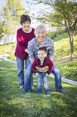 Happy Chinese Grandparents Having Fun with Their Mixed Race Grandson Outside.