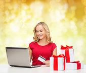 christmas, holidays, technology and shopping concept - smiling woman in red blank shirt with gift boxes, credit card and laptop computer over yellow lights background