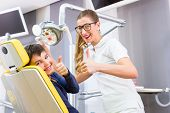 Dentist giving boy advice in dental surgery
