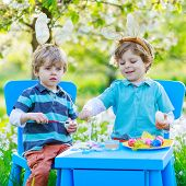 Two Little Twin Boys In Easter Bunny Ears Coloring Eggs