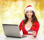 christmas, holidays, technology and shopping concept - smiling woman in santa helper hat with credit card and laptop computer over yellow lights background