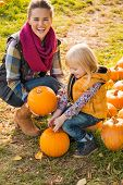 Smiling Mother And Child Choosing Pumpkins