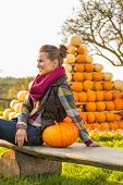 Smiling Young Woman Sitting With Pumpkin In Front Of Pumpkin Pir