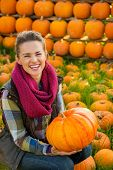 Portrait Of Happy Young Woman Holding Pumpkin In Front Of Pumpki