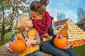 stock photo of haystacks  - Smiling mother and child sitting on haystack with pumpkins - JPG