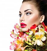 High fashion model girl with colorful flowers and red lips. Vogue style woman portrait with perfect skin. Isolated on white background. Beautiful face makeup. Glamorous lady. Vivid colours