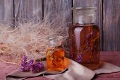 Bottle of herbal tincture and brunch of flowers on a napkin on a wooden table in front of wooden wall