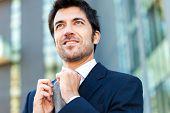 Smiling businessman adjusting his necktie