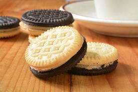 stock photo of duplex  - Closeup of duplex cream filled sandiwch cookies with a cup of coffee - JPG