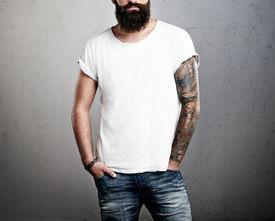 foto of hooligan  - Tattooed bearded brutal man wearing white t - JPG