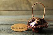 foto of bird egg  - Bird egg in wicker basket with decorative flowers on wooden background - JPG