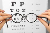 picture of medical chart  - Glasses in hands on eye chart background - JPG