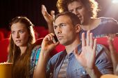 stock photo of annoyance  - Annoying man on the phone during movie at the cinema - JPG
