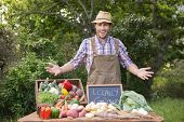 stock photo of farmer  - Happy farmer showing his produce on a sunny day - JPG