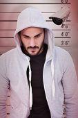 stock photo of mug shot  - Portrait of dangerous man wearing hooded jacket against mug shot background - JPG
