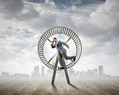 stock photo of hamster  - Young businessman running in huge hamster wheel - JPG