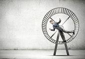 foto of hamster  - Young businessman running in huge hamster wheel - JPG