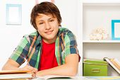 foto of homework  - Handsome boy writing in textbook doing homework at home smiling and looking at camera at his early teens - JPG