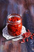image of doilies  - Goji berries in glass bottle on lace doily with silver spoon on rustic wooden table background - JPG
