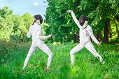 stock photo of rapier  - Two rapier fencer women fighting over beautiful nature background - JPG