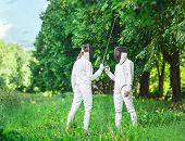 stock photo of rapier  - Two fencers women staying in park with crossed rapiers getting ready for competition - JPG