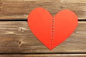 foto of staples  - Broken heart stitched with staples on wooden background - JPG