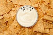 image of nachos  - weighing scales against bowl of dip placed among nachos - JPG